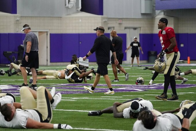 New Orleans Saints head coach Sean Payton, center, walks past quarterback Jameis Winston (2) and others as they stretch before the start of NFL football practice at TCU in Fort Worth, Texas, Wednesday, Sept. 22, 2021. (AP Photo/Tony Gutierrez)