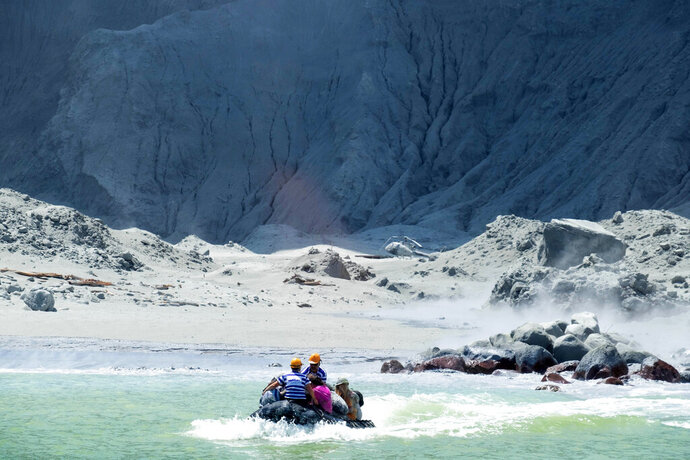 This Monday, Dec. 9, 2019, photo provided by Michael Schade shows the rescuers' boat leaving White Island following the eruption of the volcano, New Zealand. Officials say on Tuesday, Dec. 10, 2019, 47 people from New Zealand, United States, Australia, Germany, Britain, China and Malaysia were on the New Zealand volcanic island when it suddenly erupted. Of those, dozens were killed, injured or are missing. Details are scarce because conditions on the island are too dangerous for officials to return and disaster victim identification experts have only begun their work. (Michael Schade via AP)