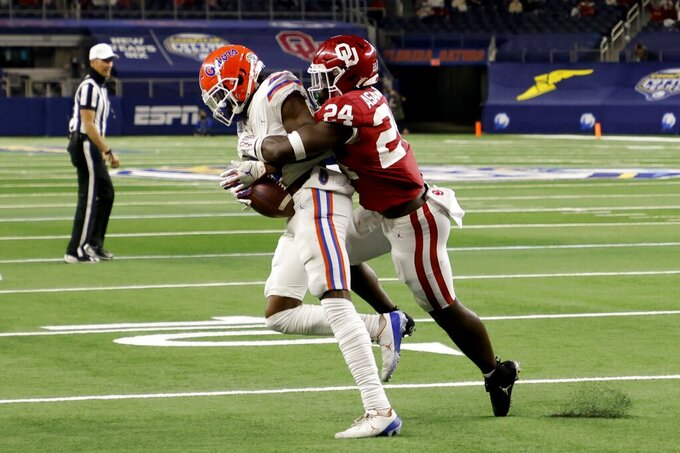 Florida wide receiver Rick Wells is stopped short of the end zone on a fourth-down play by Oklahoma linebacker Brian Asamoah (24) in the second half of the Cotton Bowl NCAA college football game in Arlington, Texas, Wednesday, Dec. 30, 2020. (AP Photo/Michael Ainsworth)