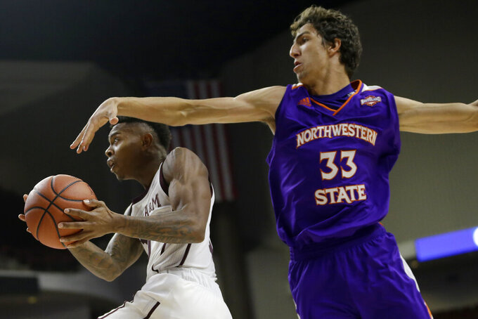 Texas A&M guard Wendell Mitchell (11) goes under the arm of Northwestern State guard Nikos Chougkaz (33) for a basket during the second half of an NCAA college basketball game Wednesday, Nov. 6, 2019, in College Station, Texas. (AP Photo/Sam Craft)