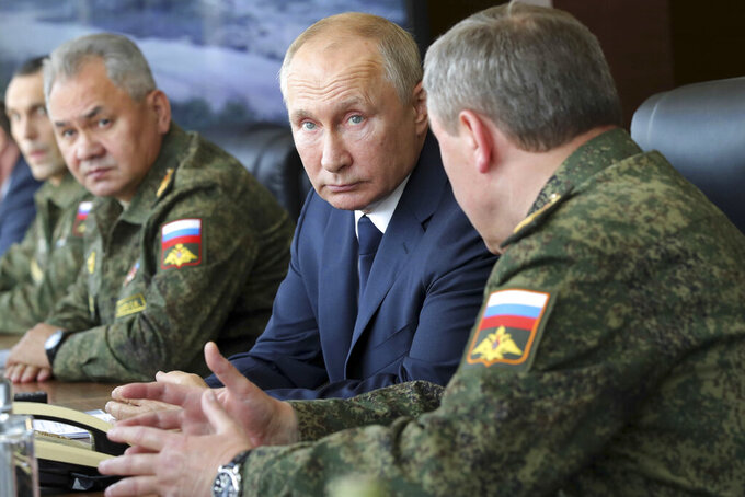 FILE - In this Sept. 25, 2020, file photo, Russian President Vladimir Putin, center, and Russian Defense Minister Sergei Shoigu, left, attend the main stage of the Kavkaz-2020 strategic command-and-staff exercises at the Kapustin Yar training ground, Russia. In an interview on Russian state television, Putin, ahead of his June 16, 2021, meeting with President Joe Biden, issued a strong, new warning that the prospect of Ukraine joining NATO was unacceptable for Russia. (Mikhail Klimentyev, Sputnik, Kremlin Pool Photo via AP, File)