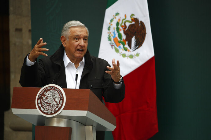 Mexico's President Andres Manuel Lopez Obrador addresses family members of 43 missing students from the Rural Normal School of Ayotzinapa, during a presentation of the ongoing investigations on the sixth anniversary of the students' enforced disappearance, at the National Palace in Mexico City, Saturday, Sept. 26, 2020. (AP Photo/Rebecca Blackwell)