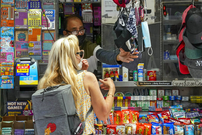 FILE — In this May 17, 2021 file photo, a woman buys a face mask at a newspaper stand in the East Village of New York. New York Gov. Andrew Cuomo and New York City Mayor Bill de Blasio have scheduled competing news conferences Monday, Aug. 2 amid rising COVID-19 case counts attributed to the highly contagious delta variant of the virus. (AP Photo/Mary Altaffer)