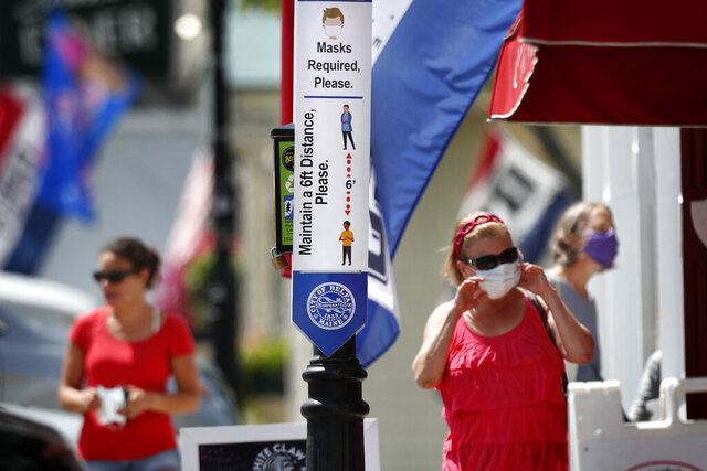 A temporary sign reminds the public to take precautions to help prevent the spread of coronavirus, Friday, July 31, 2020, in Belfast, Maine. (AP Photo/Robert F. Bukaty)
