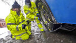 A crew from Pierce Transit puts tire chains on a metro bus in downtown Tacoma, Wash., Monday, February 11, 2019.  Schools closed across Washington state and the Legislature canceled all hearings Monday with winter snowstorms pummeling the Northwest again.  (Peter Haley/The News Tribune via AP)