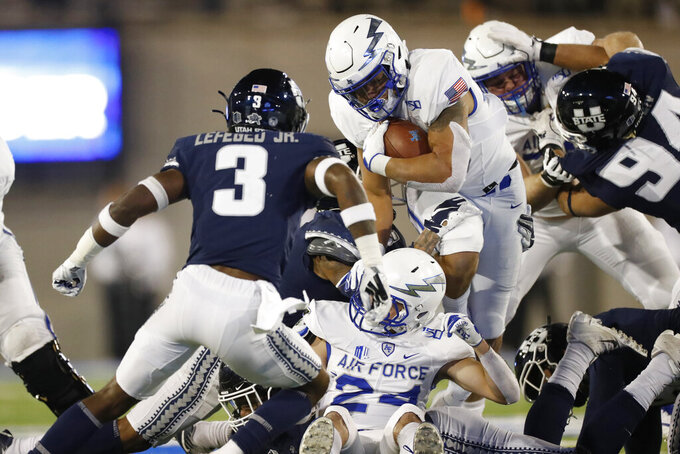 Air Force fullback Timothy Jackson, center, runs for a short gain as Utah State safety Troy Lefeged Jr., left, and defensive tackle Caden Andersen come in to make the stop in the first half of an NCAA college football game Saturday, Oct. 26, 2019, at Air Force Academy, Colo. (AP Photo/David Zalubowski)