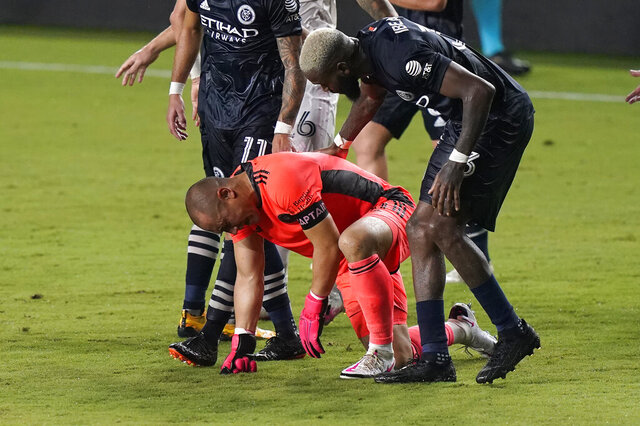 Inter Miami goalkeeper Luis Robles, left, is helped up off the pitch by New York City FC defender Sebastien Ibeagha after he collided with a NYCFC player during the second half of an MLS soccer match, Saturday, Oct. 3, 2020, in Fort Lauderdale, Fla. (AP Photo/Lynne Sladky)