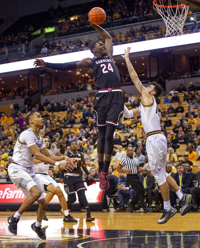 South Carolina's Keyshawn Bryant, center, dunks over Missouri's Jordan Geist, right, after he dribbles past Xavier Pinson, left, during the first half of an NCAA college basketball game Saturday, March 2, 2019, in Columbia, Mo. (AP Photo/L.G. Patterson)