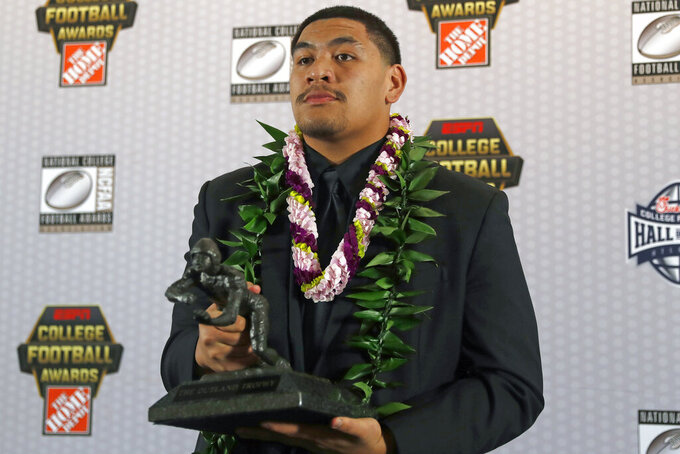 FILE - In this Dec. 12, 2019, file photo, Oregon's Penei Sewell poses with Outland Trophy for being the nation's best interior lineman, in Atlanta. Penn State linebacker Micah Parsons and Oregon tackle Penei Sewell are among 11 players selected to The Associated Press preseason All-America first-team, Tuesday, Aug. 25, 2020, who are not slated to play this fall. (AP Photo/John Bazemore, File)