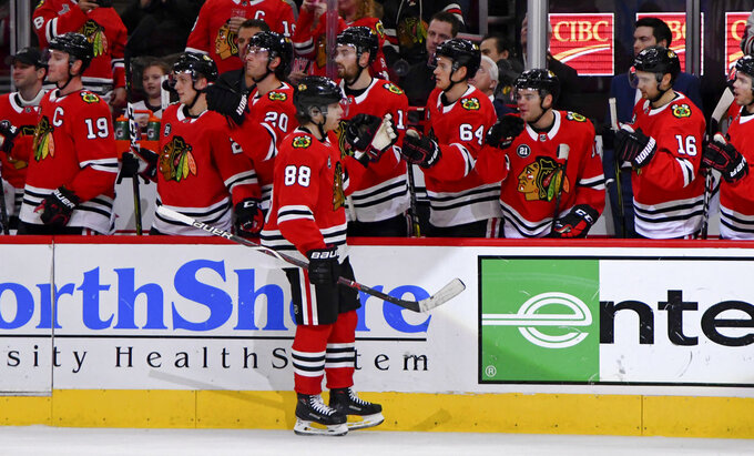 Chicago Blackhawks right wing Patrick Kane (88) celebrates with teammates after his goal against the Calgary Flames during the first period of an NHL hockey game on Monday Jan. 7, 2019, in Chicago. (AP Photo/Matt Marton)