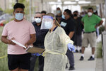 FILE - In this July 22, 2020 file photo, people line up behind a health care worker at a mobile Coronavirus testing site at the Charles Drew University of Medicine and Science in Los Angeles. A technical problem has caused a lag in California's tally of coronavirus test results, casting doubt on the accuracy of recent data showing improvements in the infection rate and number of positive cases, and hindering efforts to track the spread, the state's top health official said Tuesday, Aug. 4, 2020. (AP Photo/Marcio Jose Sanchez, File)