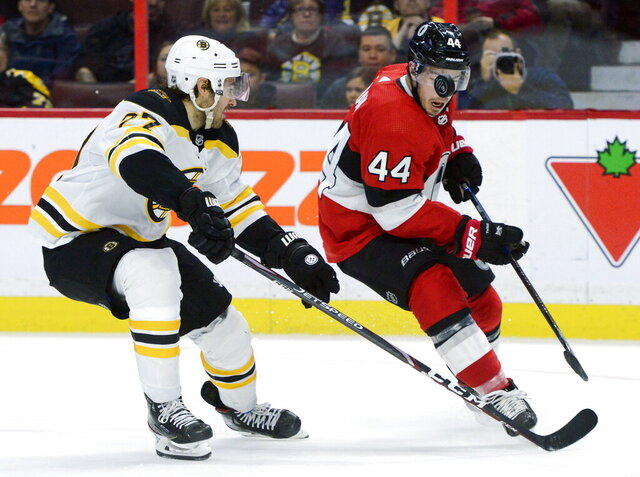 The puck floats in the face of Ottawa Senators' Jean-Gabriel Pageau as Boston Bruins' John Moore puts the pressure on during second period NHL action in Ottawa, Monday, Dec. 9, 2019. (Sean Kilpatrick/The Canadian Press via AP)