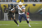 Los Angeles Chargers running back Austin Ekeler (30) runs for yardage past Jacksonville Jaguars safety Marcus Gilchrist, left, during the first half of an NFL football game, Sunday, Dec. 8, 2019, in Jacksonville, Fla. (AP Photo/Phelan M. Ebenhack)