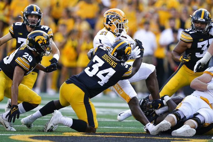 Kent State running back Joachim Bangda (21) is tackled by Iowa linebacker Jay Higgins (34) during the second half of an NCAA college football game, Saturday, Sept. 18, 2021, in Iowa City, Iowa. Iowa won 30-7. (AP Photo/Charlie Neibergall)