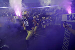 Washington quarterback Jacob Eason (10) and teammates run out of the tunnel as smoke effects go off before the team's NCAA college football game against California, Saturday, Sept. 7, 2019, in Seattle. (AP Photo/Ted S. Warren)