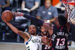 Milwaukee Bucks' George Hill tries to pass around Miami Heat's Bam Adebayo (13) during the second half of an NBA conference semifinal playoff basketball game Sunday, Sept. 6, 2020, in Lake Buena Vista, Fla. (AP Photo/Mark J. Terrill)