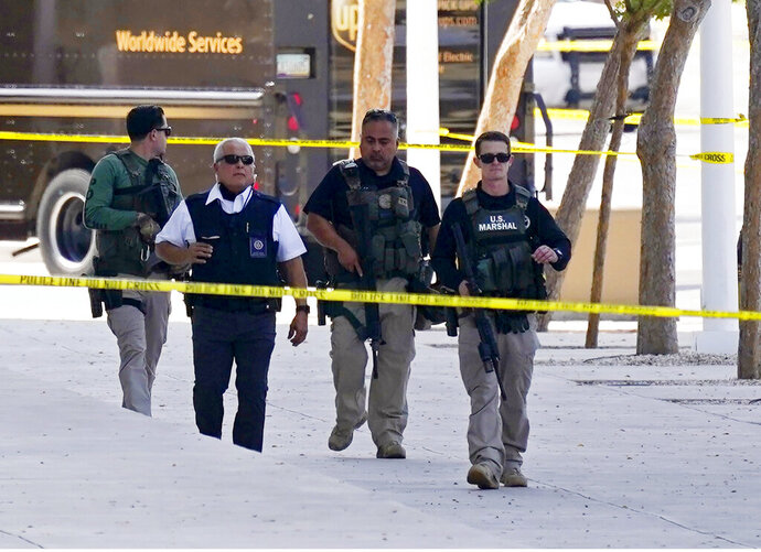 Federal law enforcement personnel patrol outside the Sandra Day O'Connor Federal Courthouse Tuesday, Sept. 15, 2020, in Phoenix. A drive-by shooting wounded a federal court security officer Tuesday outside the courthouse in downtown Phoenix, authorities said. The officer was taken to a hospital and is expected to recover, according to city police and the FBI, which is investigating. (AP Photo/Ross D. Franklin)