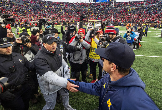 Ohio State head coach Ryan Day, front left, shakes hands with Michigan head coach Jim Harbaugh, front right, after an NCAA college football game in Ann Arbor, Mich., Saturday, Nov. 30, 2019. Ohio State won 56-27. (AP Photo/Tony Ding)
