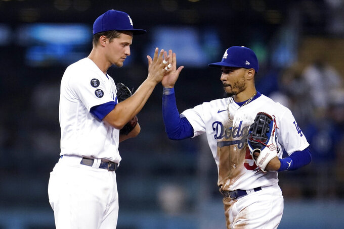 Los Angeles Dodgers' Corey Seager, left, and Mookie Betts celebrate the team's 3-2 win over the Atlanta Braves in a baseball game Tuesday, Aug. 31, 2021, in Los Angeles. (AP Photo/Marcio Jose Sanchez)