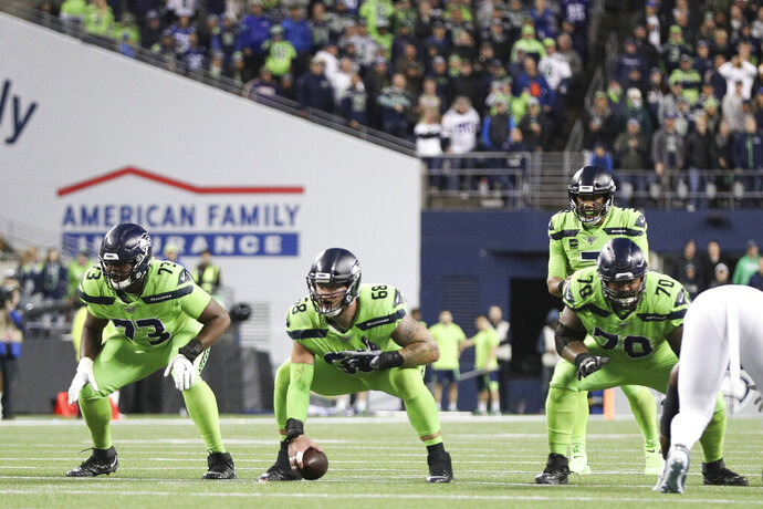 Seattle Seahawks offensive tackle Jamarco Jones (73), center Justin Britt (68) and offensive guard Mike Lupati (70) prepare for the snap to Seattle Seahawks quarterback Russell Wilson (3) during an NFL game against the Los Angeles Rams, Thursday, Oct. 3, 2019, in Seattle. The Seahawks defeated the Rams 30-29. (Margaret Bowles via AP)