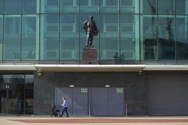 ARCHIVO - En esta foto de archivo del 9 de abril de 2020, una persona empuja una carriola frente a Old Trafford, el estadio del Manchester United (AP Foto/Jon Super)