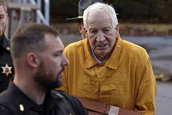 Former Penn State University assistant football coach Jerry Sandusky, right, leaves the Centre County Courthouse after attending a resentencing hearing on his 45-count child sexual abuse conviction Friday, Nov. 22, 2019. (AP Photo/Gene J. Puskar)