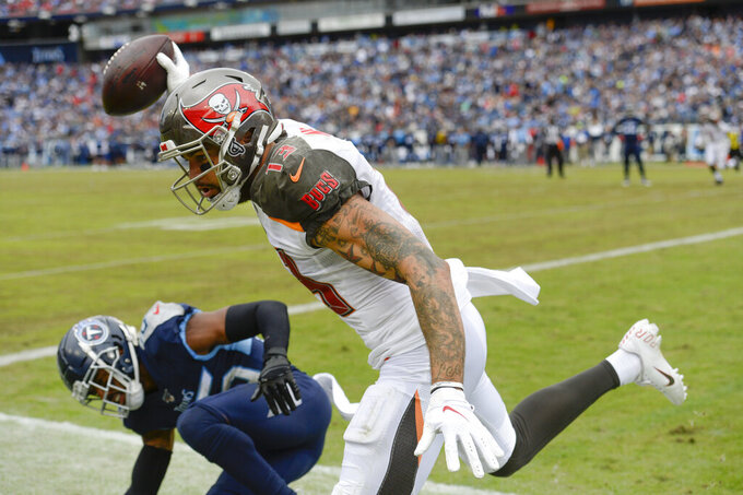 Tampa Bay Buccaneers wide receiver Mike Evans (13) scores a touchdown against Tennessee Titans cornerback Logan Ryan, left, on a 2-yard pass play in the second half of an NFL football game Sunday, Oct. 27, 2019, in Nashville, Tenn. (AP Photo/Mark Zaleski)