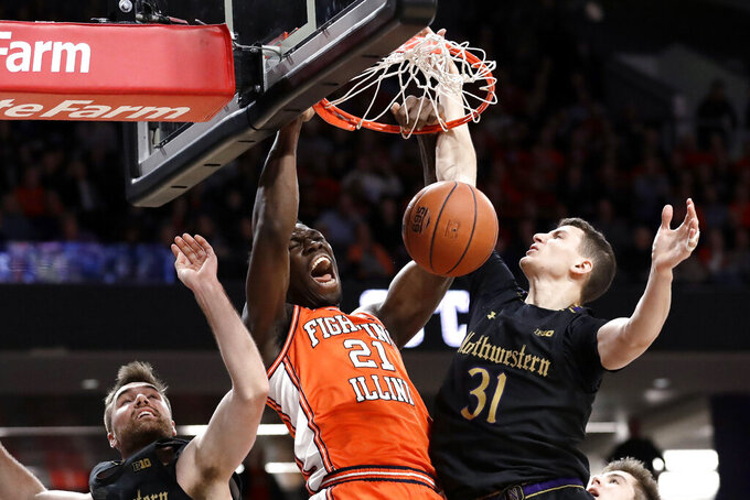 Illinois center Kofi Cockburn, center, reacts as he dunks against Northwestern guard Pat Spencer, left, and forward Robbie Beran during the first half of an NCAA college basketball game in Evanston, Ill., Thursday, Feb. 27, 2020. (AP Photo/Nam Y. Huh)