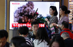 People watch a TV showing a file image of an unspecified North Korea's missile launch during a news program at the Seoul Railway Station in Seoul, South Korea, Wednesday, Oct. 2, 2019. North Korea on Wednesday fired projectiles toward its eastern sea, South Korea's military said, in an apparent display of its expanding military capabilities ahead of planned nuclear negotiations with the United States this weekend. The sign reads: