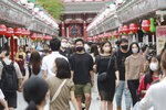 People wearing face masks to protect against the spread of the coronavirus walk through the Nakamise main path to the Sensoji temple, lined with shops in the Asakusa neighborhood of Tokyo, Friday, Aug. 13, 2021. (AP Photo/Koji Sasahara)