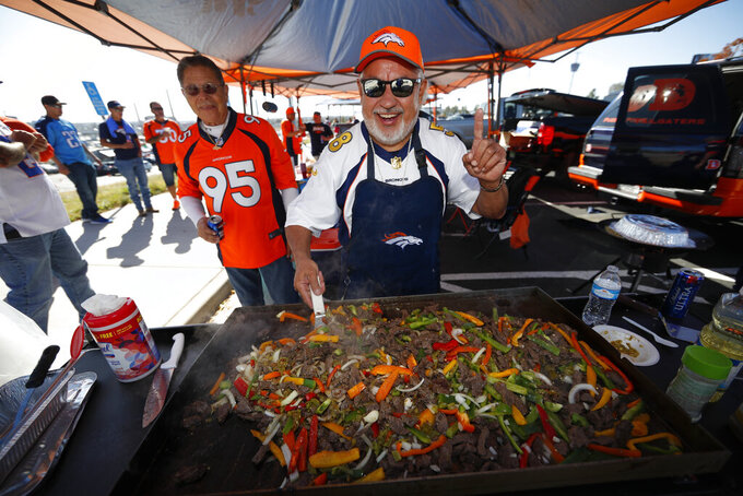 Denver Broncos fans Robert Romero, foreground, and Henry Alire, both of Pueblo, Colo., grill food as they tailgate before an NFL football game  between the Broncos and the Tennessee Titans, Sunday, Oct. 13, 2019, in Denver. (AP Photo/David Zalubowski)