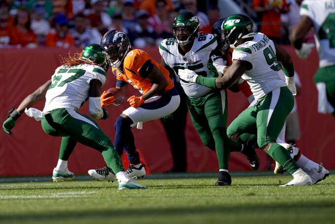Denver Broncos quarterback Teddy Bridgewater (5) tries to avoid New York Jets middle linebacker C.J. Mosley (57) during the second half of an NFL football game, Sunday, Sept. 26, 2021, in Denver. (AP Photo/David Zalubowski)