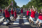 Nurses dance across the crosswalk during a red light on East Avenue near UVM Medical Center after walking out on strike Thursday morning, July 12, 2018 in Burlington, Vt.. About 1,800 unionized nurses at Vermont's largest hospital launched a two-day strike Thursday following unsuccessful contract negotiations, but hospital officials say operations continued with little disruption for patients. (Ryan Mercer/The Burlington Free Press via AP)