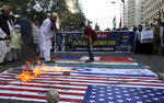 Members of a civil society group burn representations of Israeli, U.S. and Indian flags during a demonstration in support of Palestinians during the latest round of violence in Jerusalem, in Karachi, Pakistan, Tuesday, May 11, 2021. (AP Photo/Fareed Khan)