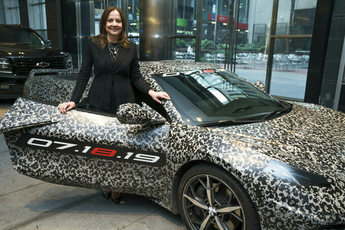 "This image provided by General Motors shows GM chairman and CEO Mary Barra standing by a camouflaged next generation Chevrolet Corvette Thursday, April 11, 2019 in New York.  A new rendition of the classic sports car is coming. General Motors has a big change in store for the eighth generation Corvette being revealed July 18, 2019. The engine in the new model is being moved from under the hood, to be tucked between the passenger compartment and the rear wheels — a ""mid-engine"" design. (Todd Plitt/GM via AP)"