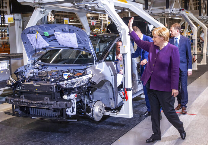 German Chancellor Angela Merkel waves to workers on the pro duction line for the production of the electric car ID.3 in Zwickau, eastern Germany, Monday, Nov.4, 2019.The vehicle is part of the new ID series with which Volkswagen is investing billions in e-mobility. (Jens Buettner/dpa via AP)