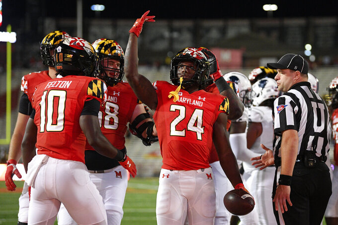 Maryland running back Roman Hemby (24) celebrates his touchdown with Tai Felton (10) and others during the second half of an NCAA college football game against Howard, Saturday, Sept. 11, 2021, in College Park, Md. (AP Photo/Nick Wass)