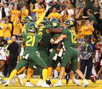 Baylor quarterback Charlie Brewer (12), right celebrates a touchdown with his teammates against Texas Tech in the second overtime of a NCAA college football game in Waco, Tex.,Saturday, Oct. 12, 2019. Baylor won 33-30. (AP Photo/Jerry Larson)