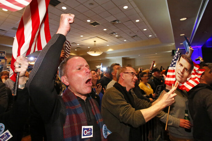 John Henninger, left, and Eric Larson, right, of Cecil Township, Pa., watches early returns at the election night party of Conor Lamb, the Democratic candidate for the special election in Pennsylvania's 18th Congressional District, in Canonsburg, Pa., Tuesday, March 13, 2018. The Pennsylvania congressional race between Democrat Conor Lamb and Republican Rick Saccone remains too close to call, with local elections officials still counting absentee ballots late Tuesday. (AP Photo/Gene J. Puskar)