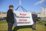 Demonstrators hold a banner during a protest outside Parliament House in Canberra, Australia, Thursday, June 17, 2021 against the prosecution of lawyer Bernard Collaery whose picture is on the demonstrator's shirt. Critics of the secret prosecutions of a former Australian spy and his lawyer argue they are another example of a government concealing political embarrassment under the guise of national security. (AP Photo/Rod McGuirk)