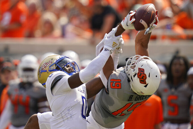 Oklahoma State wide receiver Bryson Green (19) reaches for but can't hold onto a pass while defended by Tulsa cornerback Tyon Davis (0) in the first half of an NCAA college football game, Saturday, Sept. 11, 2021, in Stillwater, Okla. (AP Photo/Sue Ogrocki)