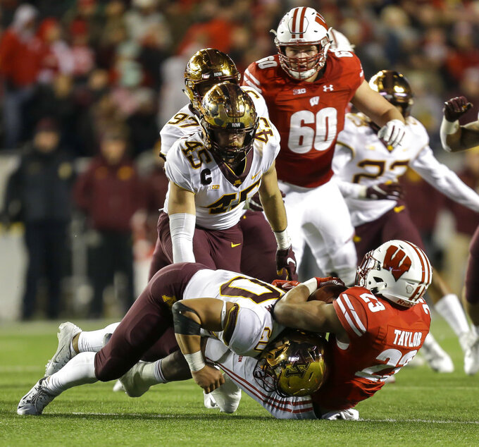 Minnesota linebacker Julian Huff (20) tackles Wisconsin running back Jonathan Taylor (23) behind the line of scrimmage during the second half of an NCAA college football game Saturday, Nov. 24, 2018, in Madison, Wis. Minnesota won 37-15. (AP Photo/Andy Manis)