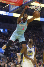 FILE - In this Feb. 10, 2020, file photo, Miami Heat forward Derrick Jones Jr. (5) dunks over Golden State Warriors guard Andrew Wiggins (22) during the first half of an NBA basketball game in San Francisco. A person with knowledge of the situation says Miami forward Derrick Jones Jr. has tested positive for the coronavirus. His result came in shortly after the Heat and other NBA teams began mandatory testing in preparation for next month's resumption of the season. Jones still plans to play when the Heat get back on the floor at the Disney complex near Orlando next month. (AP Photo/Jeff Chiu, File)