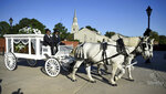 A horse-drawn hearse containing the body of opera star Jessye Norman leaves the William B. Bell Auditorium, site of her funeral, in Augusta, Ga., Oct. 12, 2019. Norman died Sept. 30 at age 74. She was awarded the National Medal of Arts, the Kennedy Center Honor and four Grammy Awards. (Michael Holahan/The Augusta Chronicle via AP)