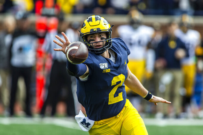 Michigan quarterback Shea Patterson (2) flicks a pass in the first quarter of an NCAA college football game against Iowa in Ann Arbor, Mich., Saturday, Oct. 5, 2019. (AP Photo/Tony Ding)