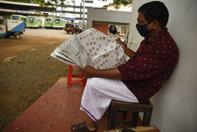 A man wearing a mask reads a newspaper at a bus terminus which has been shut down for more than a month as part of measures to curb the spread of the COVID-19 pandemic in Kochi, Kerala state, India, Wednesday, April 29, 2020. India's news publishers face a delicate balancing act as they look to offset financial losses from sinking ad sales with support from a government seeking to control the narrative on the coronavirus, sometimes by prosecuting journalists for reporting on the detrimental consequences of official pandemic policy. (AP Photo/R S Iyer)