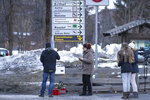 People gather near candle at the scene where a car had plowed into a group of people in Luttach, near Bruneck in the northern region South Tirol, Italy, Sunday, Germany, Jan. 5, 2020. Italian fire officials say a car crashed into a group of young German tourists in northern Italy, killing at least six people and injuring 11. (AP Photo/Helmut Moling)