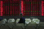 A man looks back as he monitors the stock prices at a brokerage house in Beijing, Wednesday, Jan. 9, 2019. Shares extended gains in Asia on hopes for progress in resolving the tariffs battle between the U.S. and China as talks appeared to have been extended in Beijing. (AP Photo/Andy Wong)