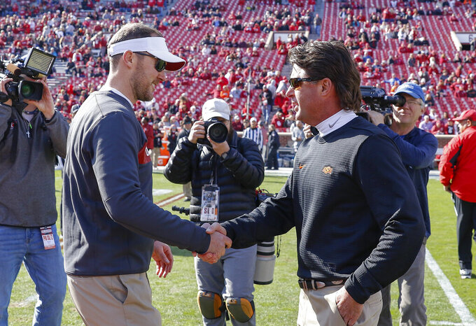 FILE - In this Nov. 10, 2018, file photo,  Oklahoma head coach Lincoln Riley, left, and Oklahoma State head coach Mike Gundy, right, meet mid field before the start of an NCAA college football game in Norman, Okla. For the four-time defending Big 12 champion Sooners, still trying to get back to the College Football Playoff for the fourth time in five seasons, Bedlam is another long standing rivalry against a Big 12 foe.   (AP Photo/Alonzo Adams, File)
