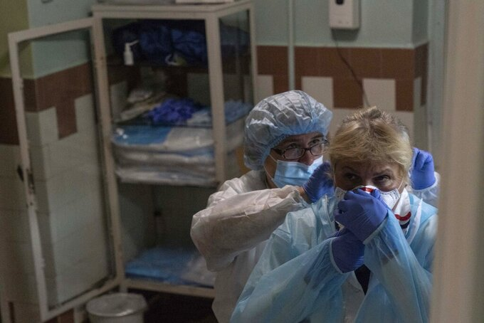 Medical workers help each other don protective suits at a hospital in Stebnyk, Ukraine, on Tuesday, Sept. 29, 2020. As coronavirus cases increase, every bed in the hospital in this city in western Ukraine is in use and its chief doctor is watching the surge with alarm and anguish. (AP Photo/Evgeniy Maloletka)